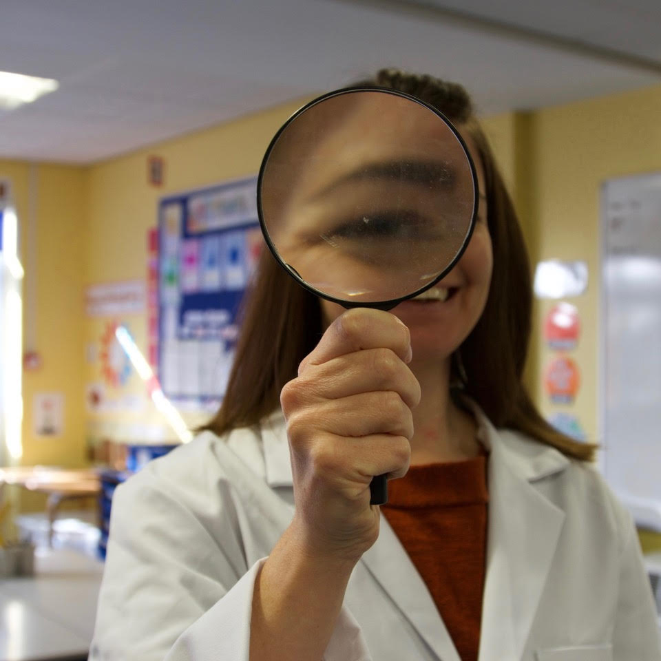 Image of Dr Jo wearing a white lab coat and holding up a large magnifying glass which is magnifying her right eye.