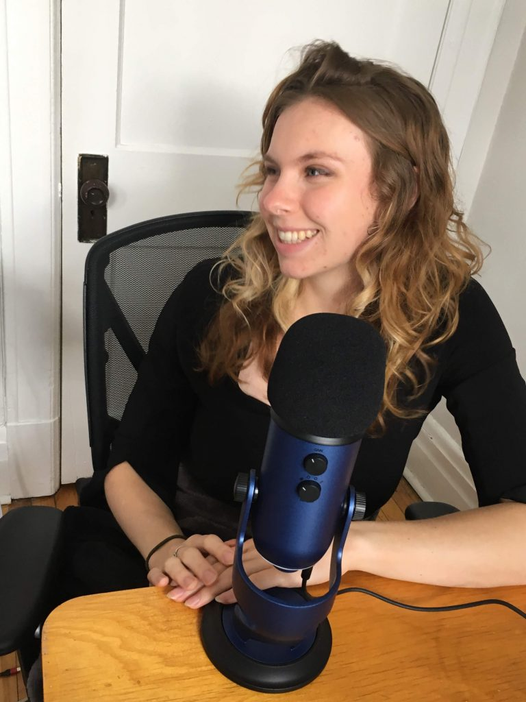 Morgan smiling, sat in front of a dark blue microphone reading to record her podcast.